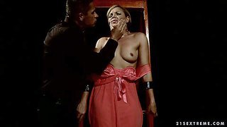 Szilvia lauren is a beautiful milf who finds herself in bondage. restrained european blonde gets punished in the dark of the dungeon. helpless woman in barely there red dress and thong gets her perky natural tits touched and her pussy vibrated.