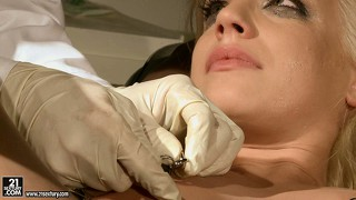 Blondie is bound on the operating table and has her tits pinched and pussy prodded