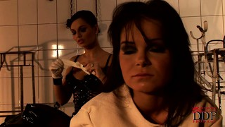Devious brunette doctor slicks up the pussy of her slave in a straightjacket