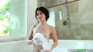 In the bathtub, a slender brunette with tiny tits satisfies her desires with a dildo