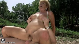 Big breasted oldie effie enjoys sex with hard dicked young guy in nature. busty granny in barely there bikini top gets her loose pussy pounded on the wild beach. she is horny for her young lover.