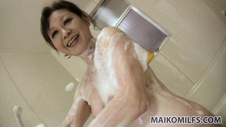 In the shower, the milf sensually washes his dick before sliding it down her throat