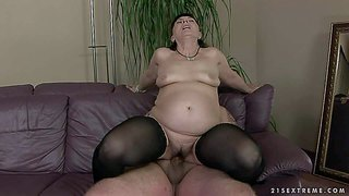 Pale dark haired mature slut with huge ass in cheep slutty stockings rides on young fat dude with tattoo and gets boned in doggy style position on leather couch in living room