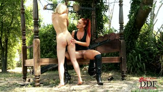 Dominatrix whips her blonde slave into submission outdoors with a paddle